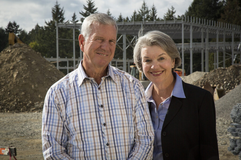 Murray and Lynda Farmer stand in front of a construction site